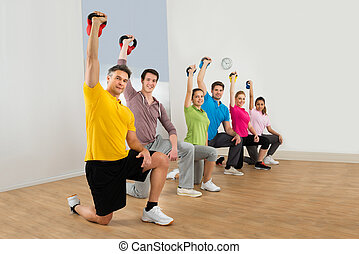 People Working Out With Kettle Bell Weights - Diverse...