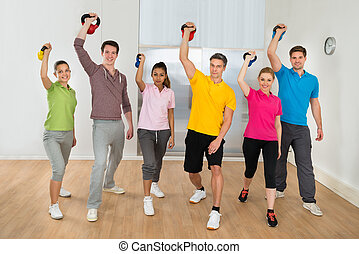 Group Of People Lifting Kettle Bell Weights - Multiethnic...