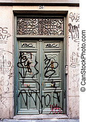 Urban decadence - Ancient building door tagged with graffiti