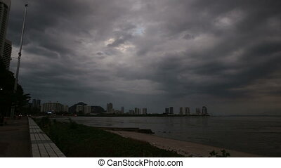 dark clouds over skyscrapers at seafront - panorama of...