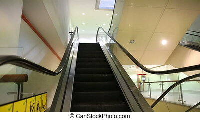modern escalator moves downward in trade mall