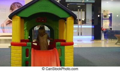 child tries to slide down from slide at toy house - little...