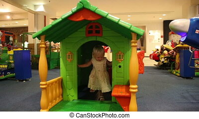 child plays at toy house in trade mall - little blonde child...