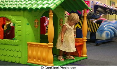child leaves toy house and go to car - little blonde child...