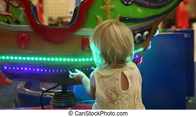 child examines boat on roundabout in trade mall - little...