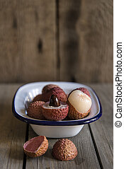 Lychees in rustic setting with wooden background