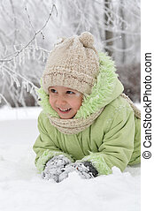 Happy little girl in warm clothes in winter outdoors