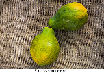 Two whole papayas on a linen background.