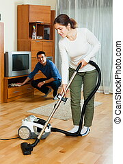 Ordinary couple doing housework together in home