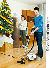 Smiling couple doing housework together in Christmas time at...