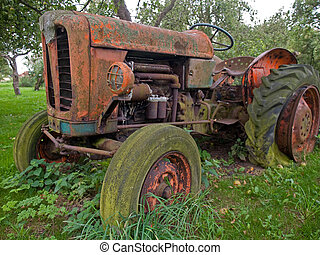 Old vintage tractor - Old rusty red vintage tractor in a...