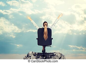 Businesswoman sitting on office chair her arms extended -...