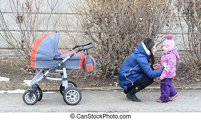 Mother with Daughter Walkin in Park with Newborn Child in...