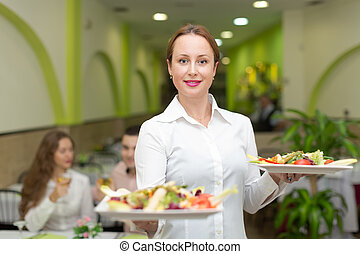 Female waiter serving guests table - Smiling female waiter...