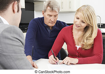 Mature Couple With Financial Advisor Signing Document At...