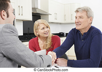 Mature Couple Shaking Hands With Financial Advisor At Home
