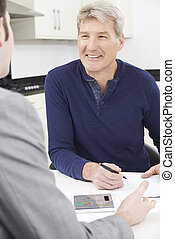 Mature Man With Financial Advisor Signing Document At Home
