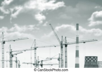 Background blurred tower cranes, chimneys, clouds -...