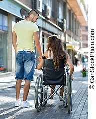 Social worker taking invalid for a walk - Young social...