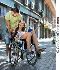 Girl in wheelchair with friend outdoor - Young caregiver and...