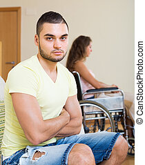 Sad man with girlfriend in invalid chair - Unhappy young man...