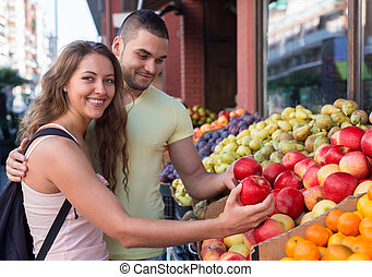 Happy couple choosing fruits from stand outdoor