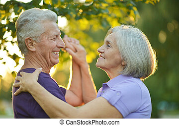 Happy Mature couple dancing in autumn park on sunset