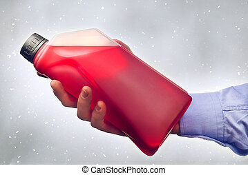 Hand Holding a Bottle of Antifreeze - Male hand holding a...
