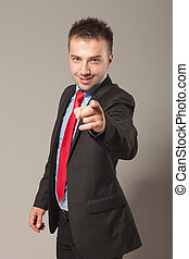 Young business man smiling while pointing at the camera. On...