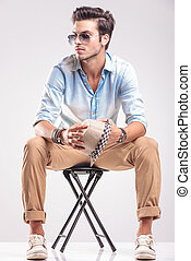 Young casual fashion man looking away while sitting on a...