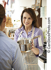 Sales Assistant In Homeware Shop Showing Customer Pan