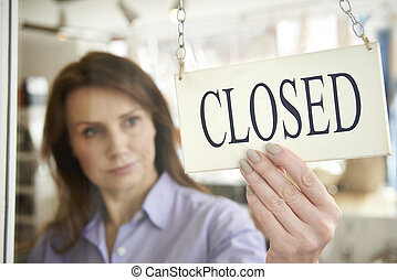 Store Owner Turning Closed Sign In Shop Doorway