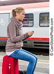 woman waiting for train and writes sms