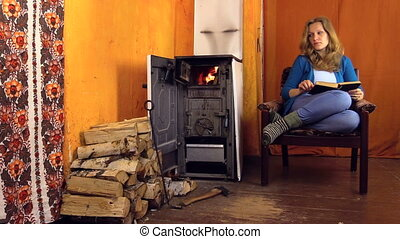 woman read book stove - Woman sitting on armchair at home on...