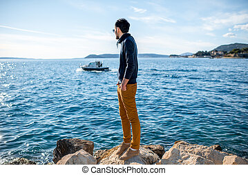 Man watching boat on the sea - Man watching boat floating on...