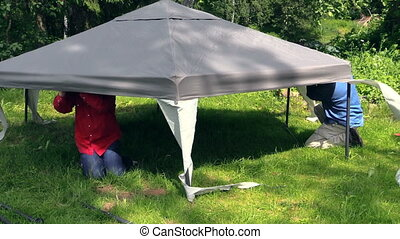 men fix gazebo top - men crawled under the gazebo canvas top...