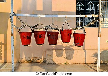 Five fire buckets hanging on a wall in India - Five fire...