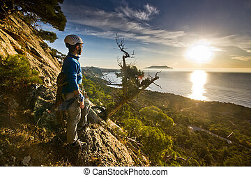 rock climber standing near tree looking on sunrise - rock...