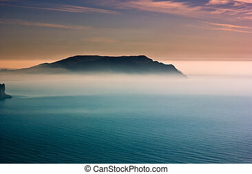 colorful sunrise with haze above cape in Black Sea with blue...