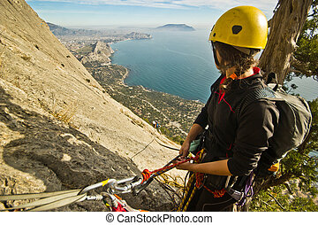 rock climbers ascend the mountain - two rock climbers ascend...