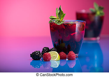 Raspberry and blackberry cocktail with mint garnish Studio...
