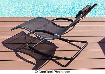 Pool side chaise lounge - a chaise lounge on the pool side...