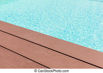 Pool side - wooden planks at the pool side with vibrant pool...