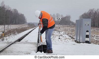 Worker clean the rails with a snow