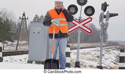 Man with cell phone and snow shovel near signal beacons