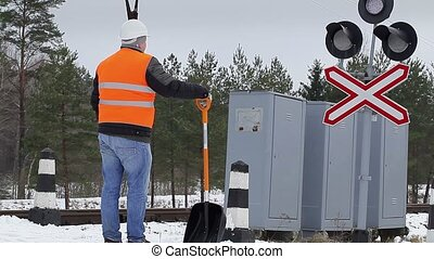 Worker working with snow shovel near signal beacons