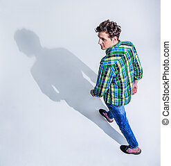 Top view portrait of a young man in colourful wear walking...