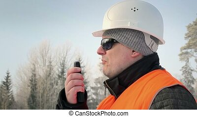 Forest inspector talking on a walkie-talkie in the woods