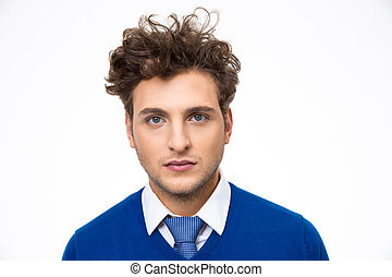 Serious young man with curly hair over gray background