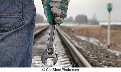 Man with adjustable wrench on the railroad in winter